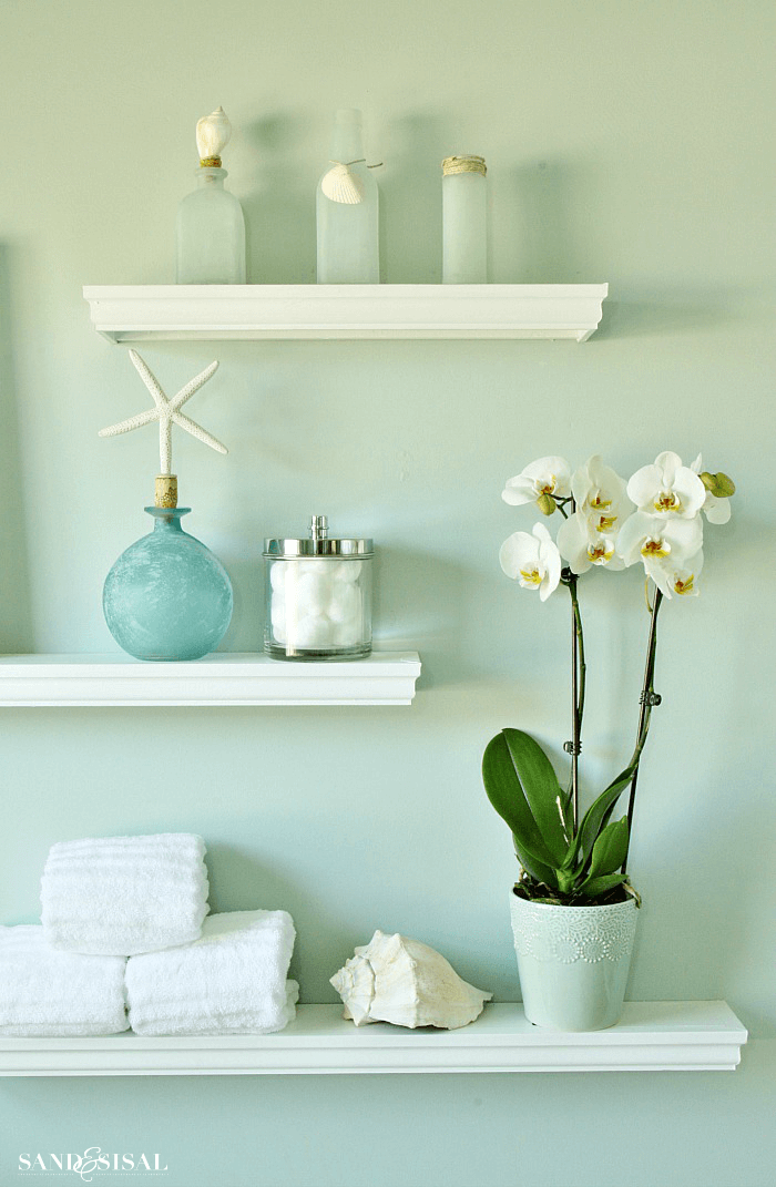 Bathroom shelves decor with white orchid flower arrangements