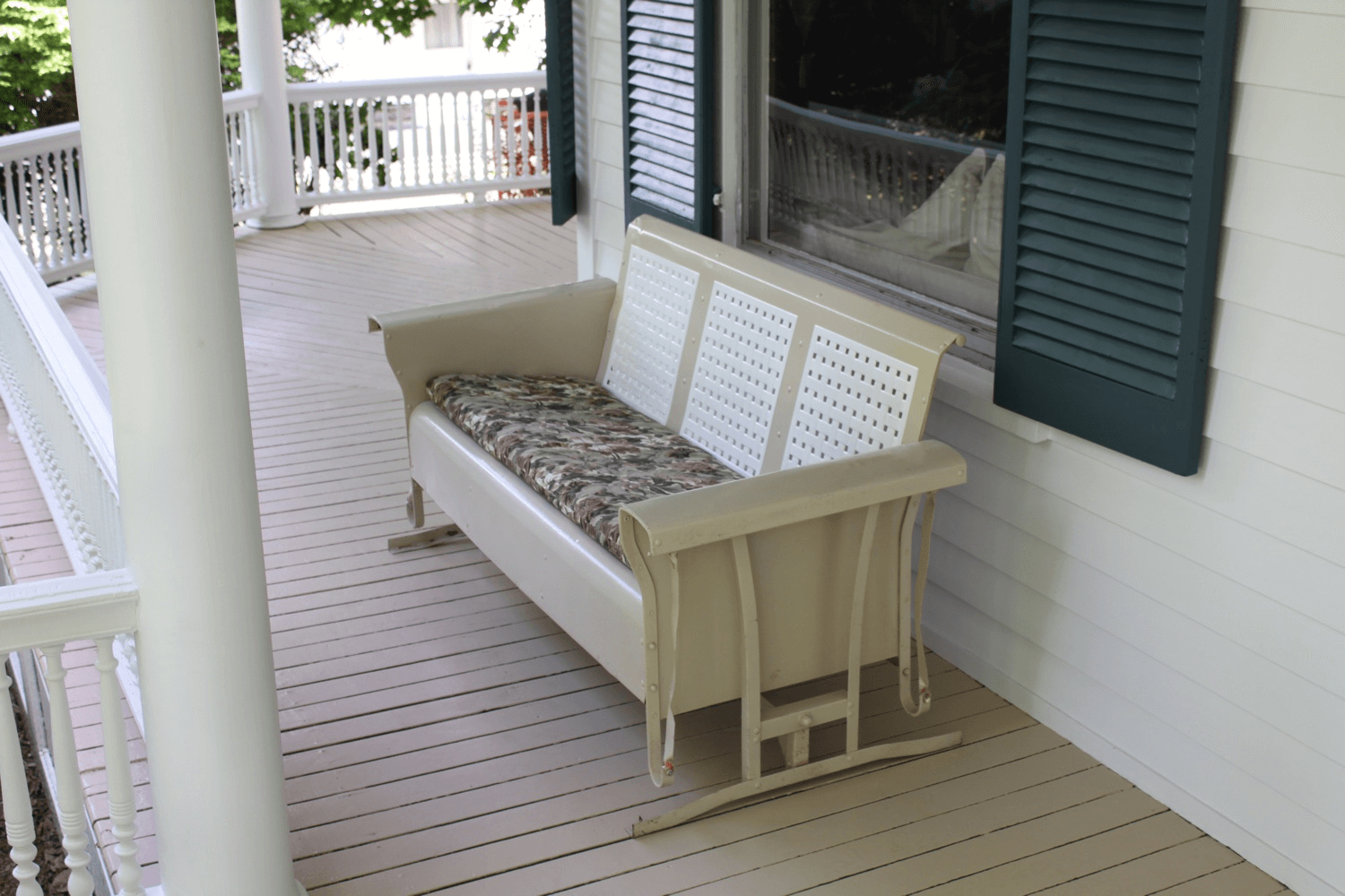 Gray front porch glider bench with cushions