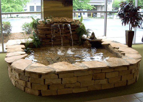 Indoor fish pond with fountain and waterfall