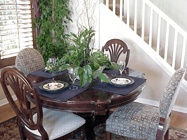How to Decorate Black Dining Table with natural flower and glass in the narrow space under stairs