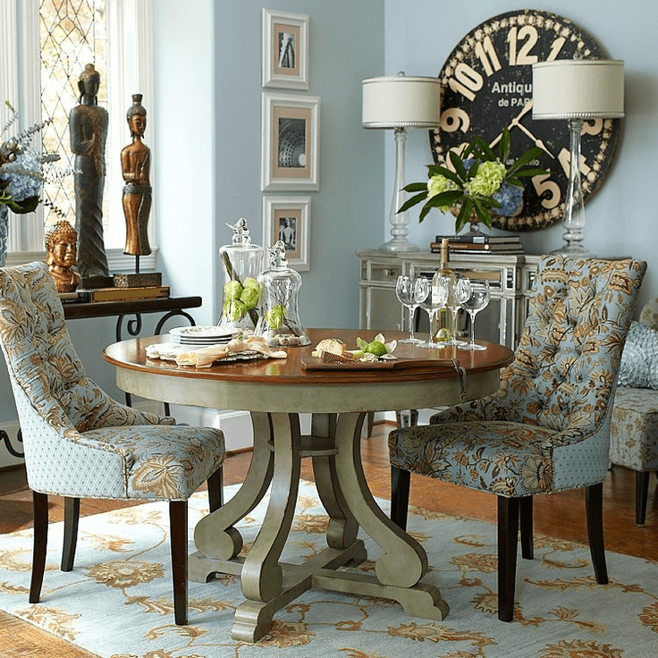 Rustic round table dining room decor with charger, glass, and uniquie statue and large wall clock