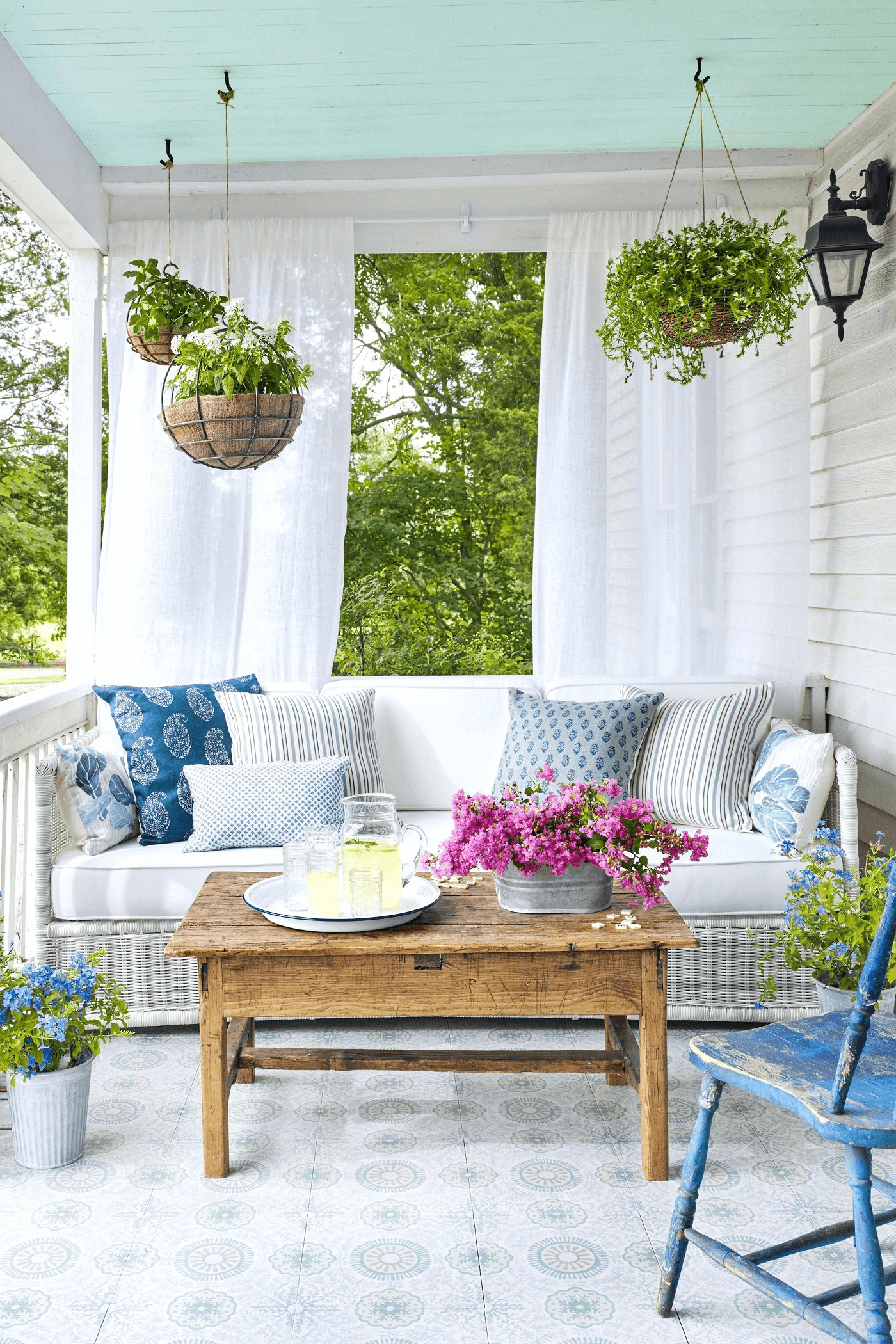 Rustic small front porch decorating ideas for summer with flower pot and colorful pillow Bright Patterned Cushions